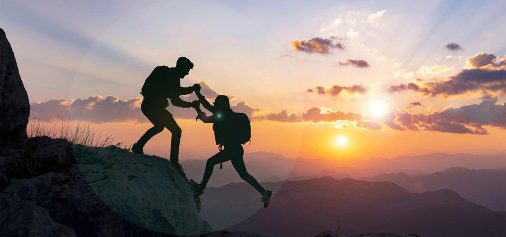 coach helping student climb a mountain